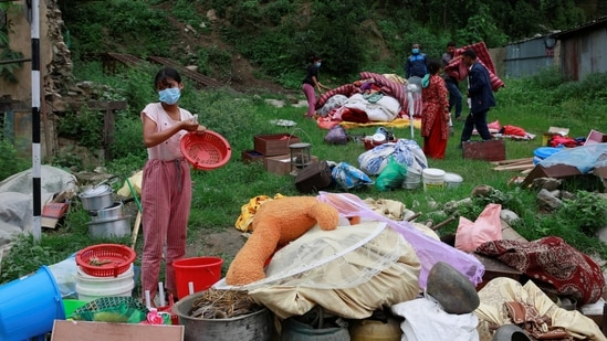 Locals gather their belongings as they move towards higher ground from the flood-affected area in Sindhupalchok, on June 16. Nearly 200 families residing along the Melamchi River Corridor have been displaced from their homes and have been taking shelter in a local school since June 15 evening, ANI reported.(Navesh Chitrakar / REUTERS)