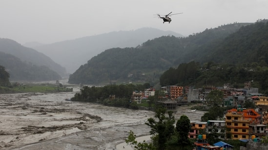 A Nepal Army helicopter flies above the swollen Melamchi river during a rescue mission in Sindhupalchok, on June 16. The Nepal Army along with Armed Police Force and the Nepal Police has been conducting a rescue and search operation in the flood-ravaged area, which continues to be submerged under a thick layer of mud and high flowing water.(Navesh Chitrakar / REUTERS)