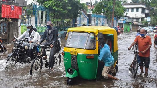 A driver tries to pull his three-wheeler out of a waterlogged street after heavy rain in Kolkata onThursday, June 17. (PTI)