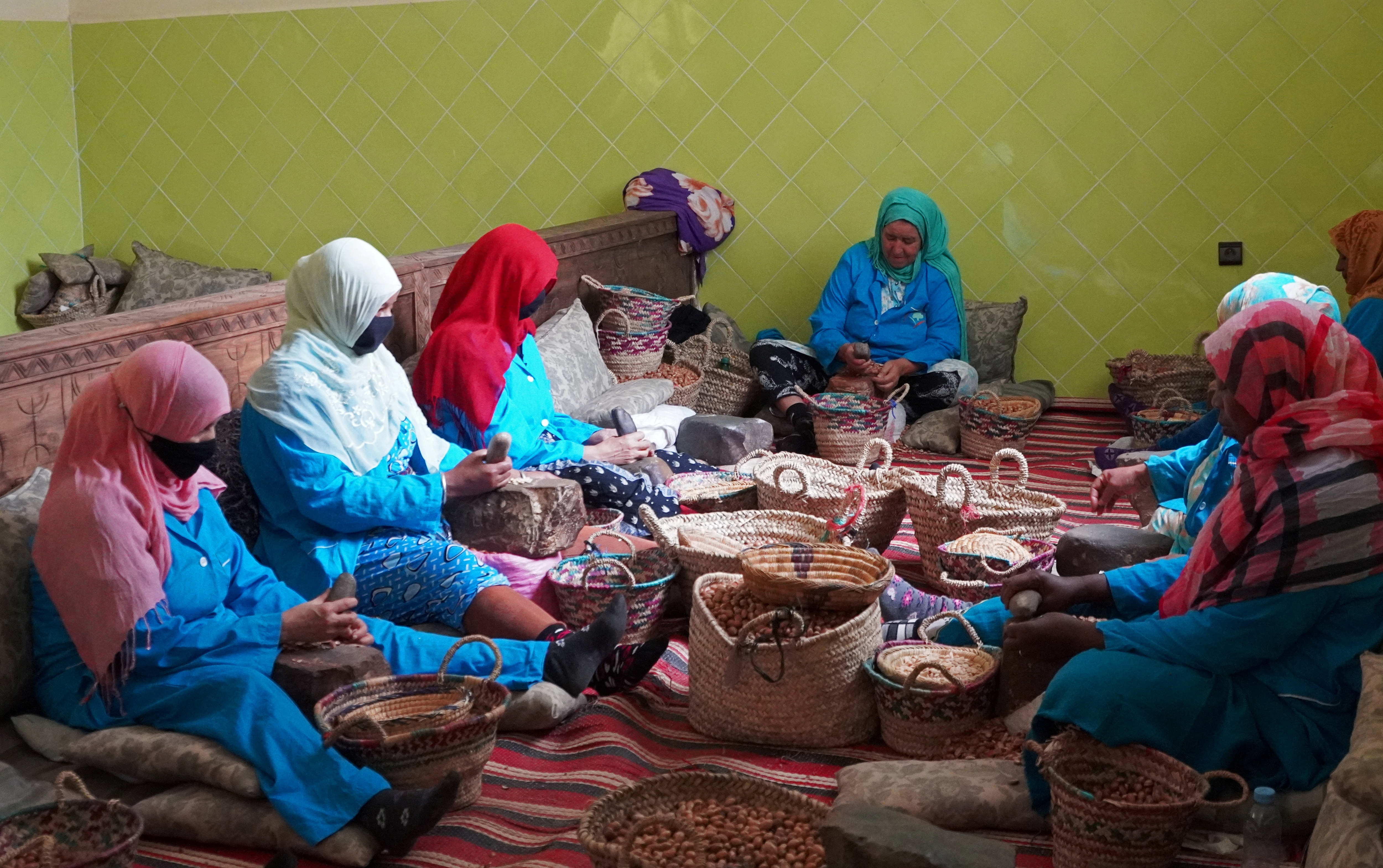 Amazigh women sit together as they crush argan nuts to extract the kernels, at Women's Agricultural Cooperative Taitmatine, in Tiout, near Taroudant, Morocco June 10, 2021. (REUTERS)