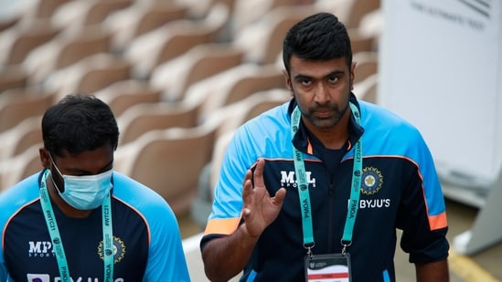 India's Ravichandran Ashwin, right, walks with a member of team support to cross over on the other side of field after rain delayed start of the first day of the World Test Championship final cricket match between New Zealand and India, at the Ageas Bowl in Southampton, England, Friday, June 18, 2021.(AP)