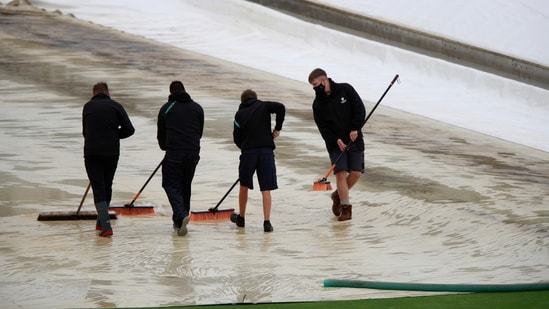 Groundsmen clear water of the covers protecting the pitch after the rain-delayed start of the first day of the World Test Championship final cricket match between New Zealand and India, at the Ageas Bowl in Southampton.(AP)