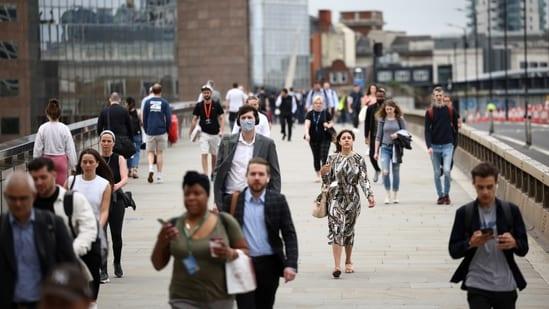 People walk across London Bridge during morning rush hour, in London, Britain, June 11, 2021. (REUTERS)