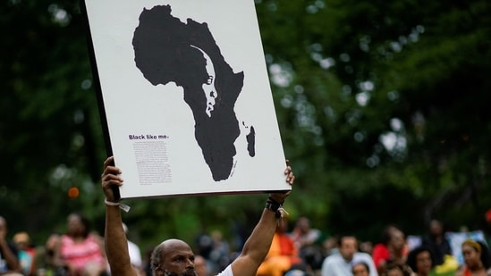 A man holds a banner as people gather at St. Nicholas Park to celebrate Juneteenth, which commemorates the end of slavery in Texas, two years after the 1863 Emancipation Proclamation freed slaves elsewhere in the United States, in New York City, (REUTERS)