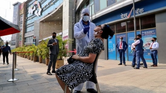 A healthcare worker collects a swab sample from a woman during a rapid antigen testing campaign for coronavirus disease (Covid-19), outside a shopping mall in Mumbai.(REUTERS)