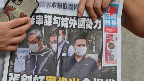 A supporter of two executives from Hong Kong's pro-democracy Apple Daily newspaper, chief editor Ryan Law and CEO Cheung Kim-hung, holds up a copy of the newspaper during a protest outside court in Hong Kong.(AFP)