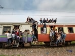 Commuters hang on the gates and sit on the roof while traveling by a crowded train. (PTI Photo)