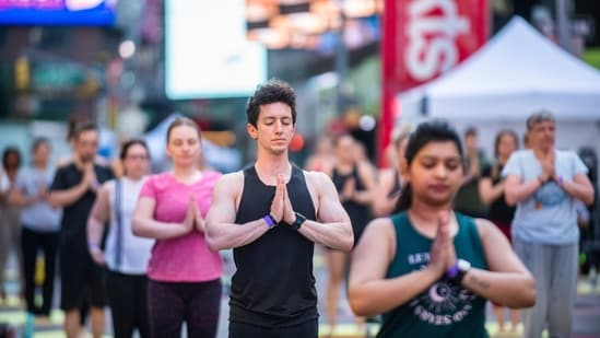 People participate in Solstice in Times Square: Mind Over Madness Yoga, an annual all-day outdoor yoga event in New York's Times Square, Sunday, June 20, 2021. (AP Photo/Brittainy Newman)