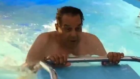 Dharmendra practices water aerobics in his swimming pool.