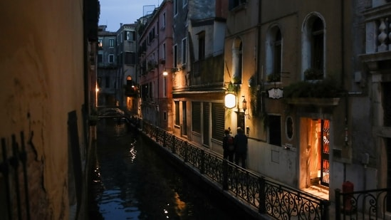 A couple walk near a canal in Venice, Italy. UNESCO has recommended adding Venice to its endangered heritage list.(Reuters File Photo.)