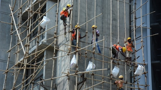Workers standing on a bamboo scaffolding working at a construction site after business took a hit during Covid-19 pandemic, in Thane. (HT Photo)