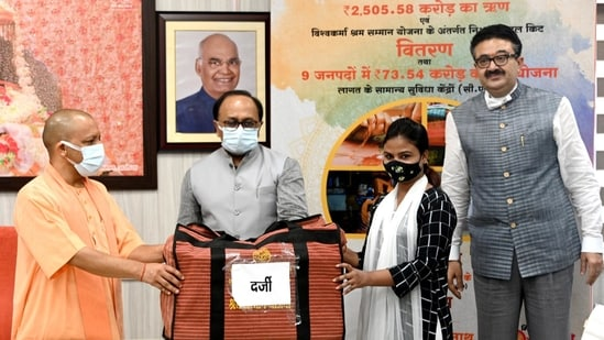 Uttar Pradesh Chief Minister Yogi Adityanath distributes loans and tool kits to beneficiaries during an online swarozgar Sangam at his official residence in Lucknow. (ANI Photo)