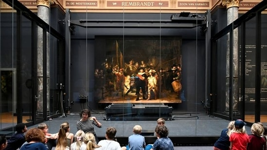 Children look at Rembrandt's famed Night Watch, which is back on display in what researchers say in its original size, with missing parts temporarily restored in an exhibition aided by artificial intelligence, at Rijksmuseum in Amsterdam, Netherlands June 23, 2021. REUTERS/Piroschka van de Wouw(REUTERS)