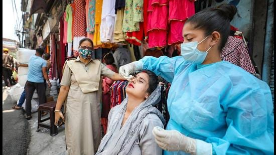A health worker collects a nasal sample from a woman for Covid-19 testing at a market in Jammu. (File photo)