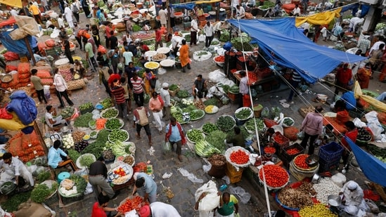 People shop at a crowded wholesale vegetable market after authorities eased coronavirus restrictions, following a drop in Covid-19 cases, in the old quarters of Delhi.(REUTERS)
