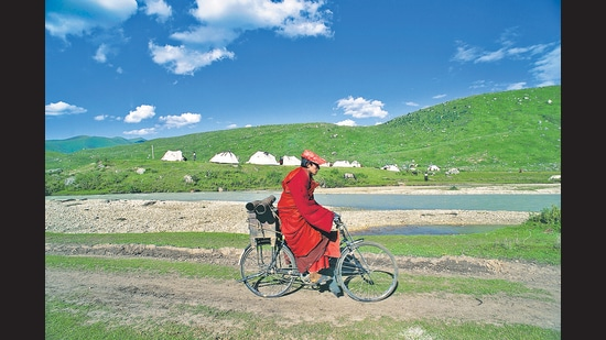 A monk cycling in the Kham region of Western Sichuan in Tibet. (De Agostini via Getty Images)