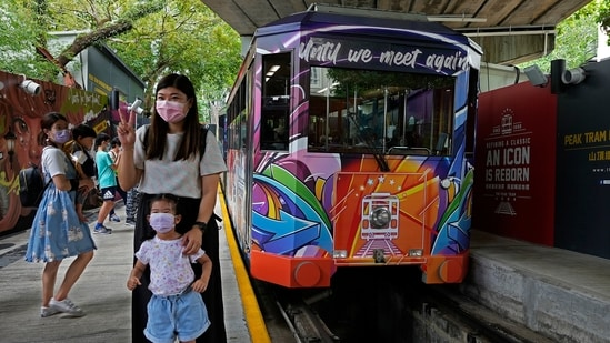 Passengers pose next to a Peak Tram on June 16, 2021. Hong Kong's Peak Tram is a fixture in the memories of many residents and tourists, ferrying passengers up Victoria Peak for a bird's eye view of the city's many skyscrapers. (AP)