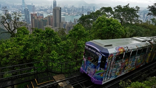 A Peak Tram passes an uphill of the Victoria Peak with a backdrop of Hong Kong on June 17, 2021. (AP)