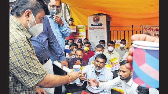 Maharashtra education minister Uday Samant offers lime water to professors protesting outside the Central building in Pune on Sunday. (HT PHOTO)