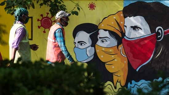 People walk past a graffiti depicting awareness on masks. (Photo by Pratik Chorge/Hindustan Times)