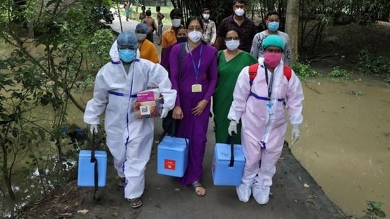 Healthcare workers carry Covishield doses to inoculate villagers during a door-to-door vaccination and testing drive in West Bengal.(Reuters Photo)