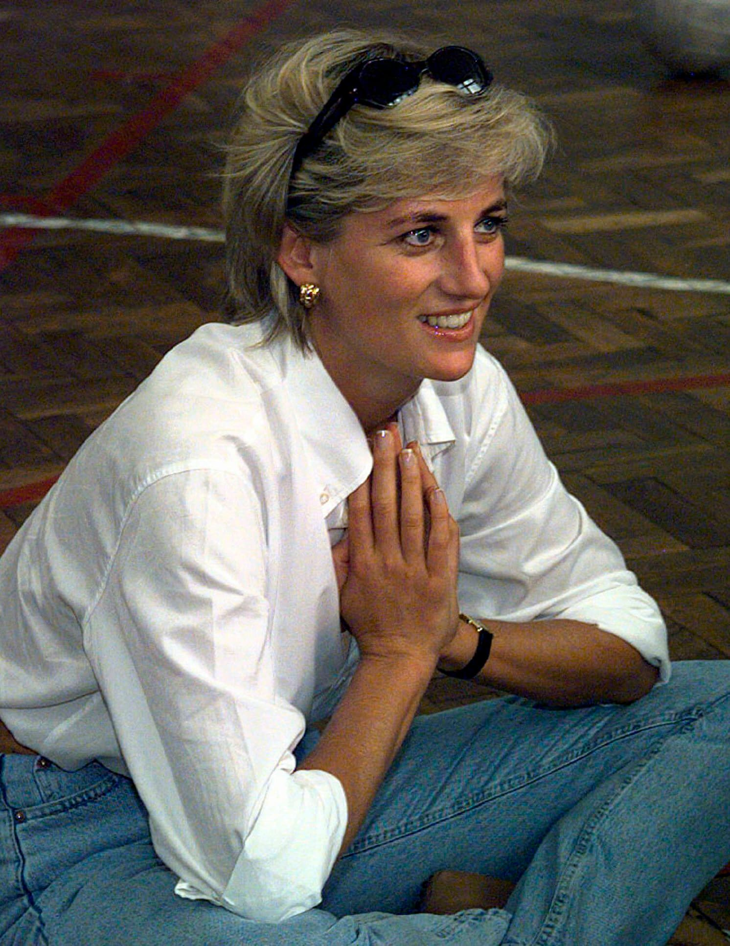 The Princess of Wales sits and talks to members of a Zenica volleyball team who were injured by landmines during her visit to Zenica, Bosnia.  She believed in fashion classics for these informal minimalist looks.  A white shirt with mommy jeans and gold earrings does the trick here.  (PA)