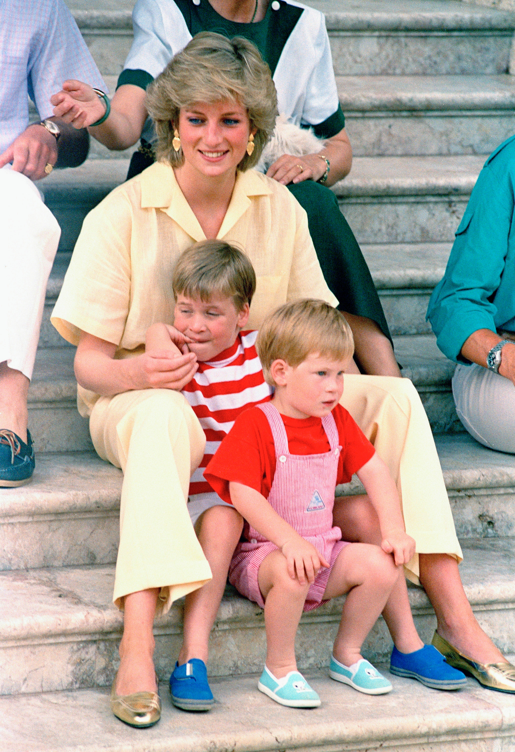 British Princess Diana of Wales smiles as she sits with her sons, Princes Harry, in the foreground, and William, on the steps of the Royal Palace on the island of Mallorca, Spain.  In a monotonous style, she adds a touch of glitter with her accessories.  (PA)