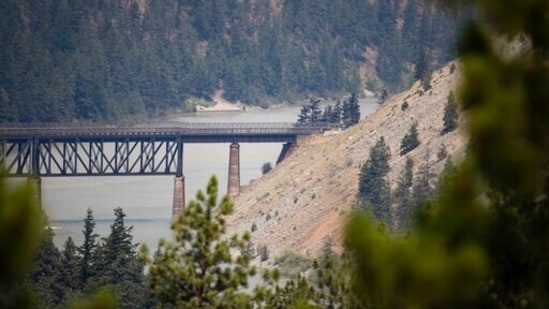 A rail bridge spans the Fraser River as a wildfire burns in Lytton, British Columbia, Friday, July 2, 2021. (Darryl Dyck/The Canadian Press via AP)