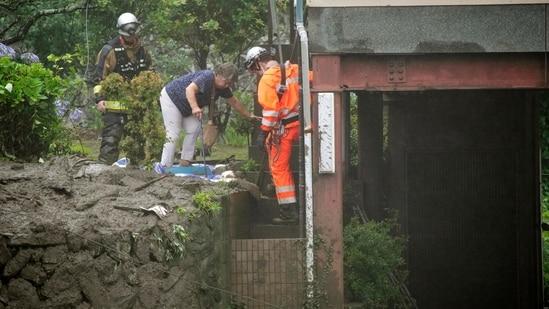 Los bomberos ayudan a evacuar a un residente después de un deslizamiento de tierra en el distrito Isuzu de Atom el 3 de julio.  Se emitieron alertas de salida para un área amplia conocida como