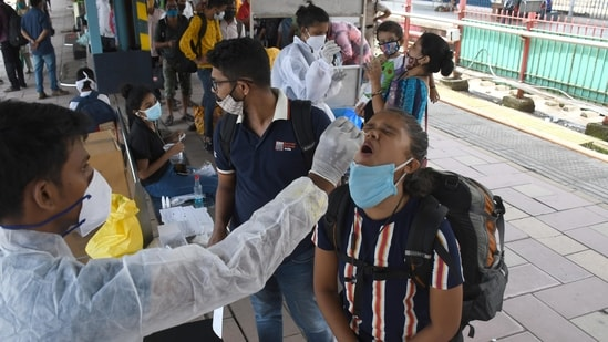 A medic collects swab samples for Covid-19 test of passengers arriving at Dadar station, in Mumbai on Saturday.(Bhushan Koyande/HT Photo)