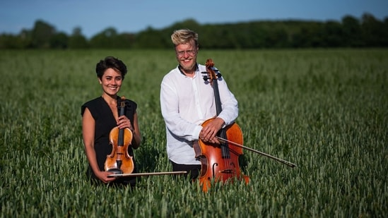 """Cellist Jacob Shaw (R) and violinist Roberta Verna pose for a picture on a corn field on June 15 in Stevns, Denmark. Verna, a 22-year-old violinist, came to Stevns to """"get a different perspective on things."""" Verna, together with Shaw, played pieces by Reinhold Gliere and Bela Bartok for the ruminants, who were seemingly as moved by the beauty of the melody as they were by the distribution of food.(Jonathan Nackstrand / AFP)"""