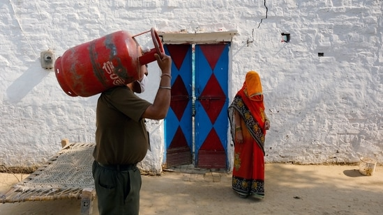 A worker delivers an LPG cylinder to a village home in Greater Noida.(Bloomberg Photo)