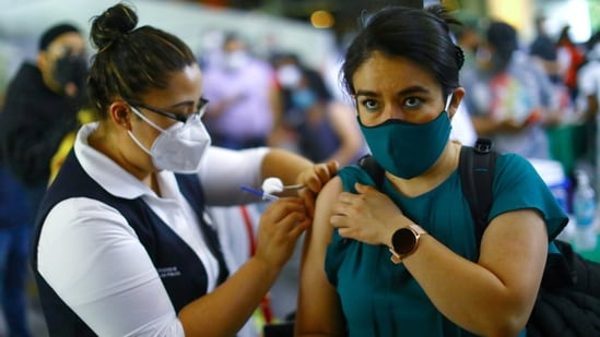 A woman receives a dose of the AstraZeneca coronavirus disease vaccine during a mass vaccination in Mexico City.(Reuters Photo)