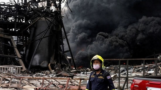 Emergency personnel looks on as smoke rises from a plastic factory after an explosion in Samut Prakan, outside Bangkok, Thailand. (Reuters)