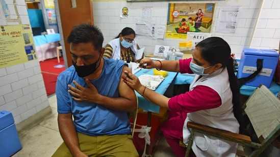 A healthcare worker administering a dose of Covid-19 vaccine to a beneficiary, at a government dispensary in New Delhi.(Raj K Raj / HT Photo)