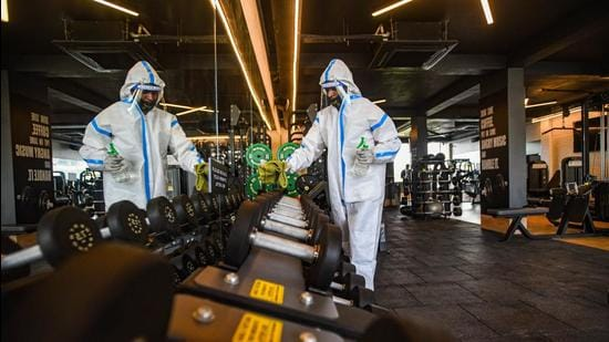 A worker in PPE coveralls chemically disinfects equipment in a gym ahead of its reopening under unlock guidelines in New Delhi. (Representational image/HT Archive)