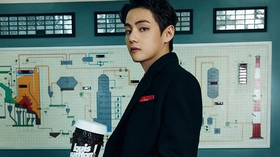 BTS member V sported a long coat and had a Louis Vuitton monogrammed coffee cup in his hand, a black messenger bag from the collection was seen placed on the desk beside him.(Instagram)