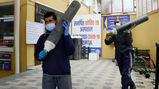Health workers carrying oxygen cylinders from a store in a hospital in Shimla. (Deepak Sansta/HT File Photo)