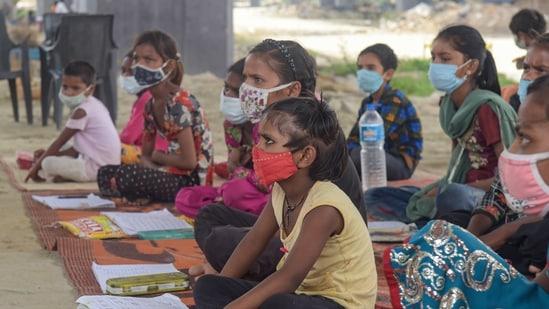 Students from a slum area attend an open-air tuition class at Panchsheel Shikshan Sansthan, at Yamuna Khadar Mayur Vihar, in New Delhi, June 10, 2021. (PTI)
