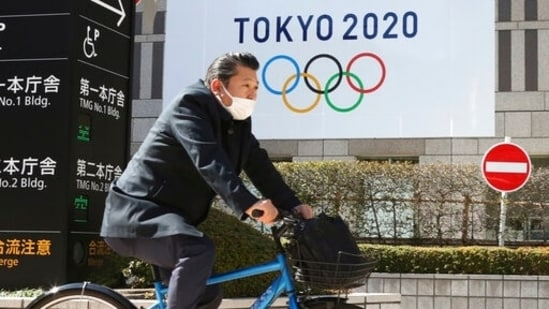 A man wearing a face mask cycles past the logo of the Tokyo Olympics, in Tokyo.(AP)