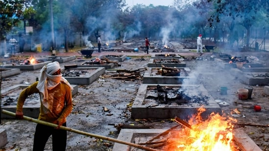 A worker stoking a funeral pyre during cremations of Covid-19 victims at Sarai Kale Khan crematorium, in New Delhi, India, on Thursday, May 06, 2021. (Photo by Amal KS / Hindustan Times)