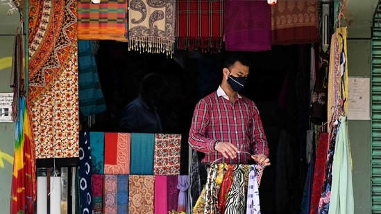 A vendor wearing a facemask as a preventive measure against the spread of the Covid-19 coronavirus, opens his shop at a market in New Delhi.(AFP)