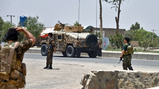 Afghan security personnel stand guard along the road amid ongoing fight between Afghan security forces and Taliban fighters in Kandahar on July 9, 2021. (AFP)