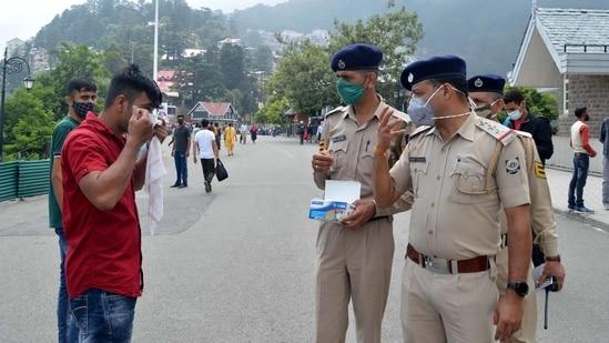Police personnel warning tourists to wear face masks at Ridge, Shimla on Saturday, (Photo by Deepak Sansta / Hindustan Times)