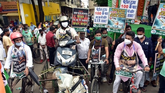Trinamul Congress supporters pull a scooty on a tri-cart and others ride bicycles during a demonstrative protest against fuel price hikes at a petrol pump, in Kolkata on Saturday. (ANI Photo)