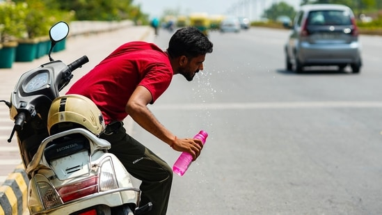 A man washes his face to cope with the heat at Safdarjung flyover, in New Delhi on Saturday.(ANI Photo)