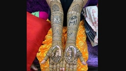The image shows the bride sporting Manchester United and Mumbai Indians logos mehendi design.