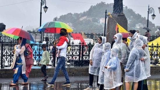 Shimla, India July 12: Tourists in raincoats and others walking with umbrellas during the rain at Ridge, Shimla, Himachal Pradesh, India on Monday, July 12, 2021.(Photo by Deepak Sansta / Hindustan Times)