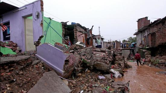 Local residents inspect the debris of their houses that were damaged by flash floods after heavy monsoon rains on the outskirts of Jammu on Monday. (AFP)