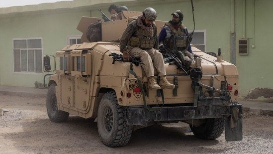 Members of Afghan Special Forces climb down from a humvee as they arrive at their base after heavy clashes with Taliban during the rescue mission of a police officer besieged at a check post in Kandahar province in Afghanistan.(Reuters)
